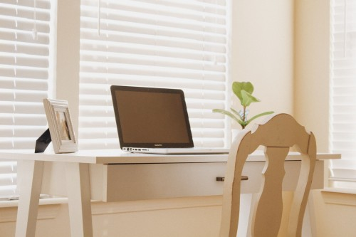 laptop-on-woodendesigned-table-and-chair-near-white-wall-and-plant-pot-inside-home-office-photo.jpg