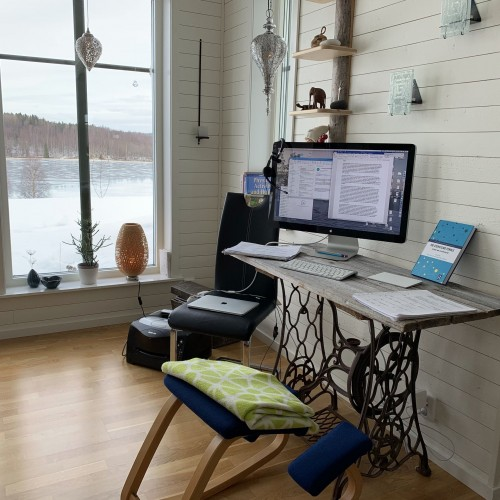 paper-books-and-black-laptop-computer-on-brown-wooden-table-with-blue-stool-near-white-wall-and-window-inside-home-office.jpg