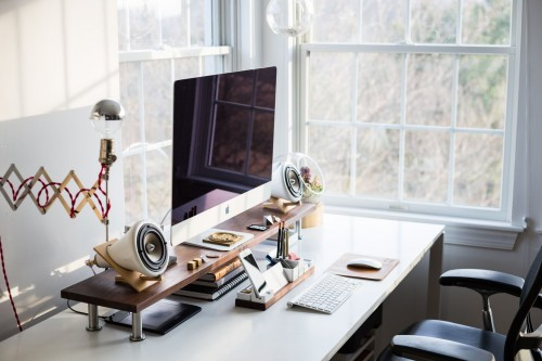 silver-iMac-and-white-speaker-and-modern-table-lamp-on-desk-near-window-home-office-photo.jpg