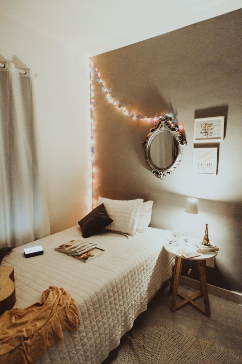 table-beside-white-bed-and-trown-pillow-on-it-near-window-and-mirror-on-white-wall-photo.jpg