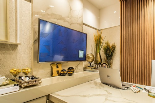 turned-on-flat-screen-TV-on-white-wall-near-table-lamp-and-wooden-wall-and-potted-plant-at-corner-photo.jpg