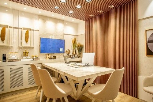 turned-on-flat-screen-tv-on-wall-rack-near-white-table-set-inside-brown-wooden-designed-wall-photo.jpg