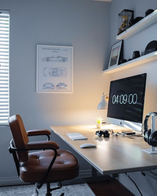 turned-on-iMac-and-table-lamp-on-brown-wooden-table-with-chiar-near-wall-with-shelf-inside-office.jpg