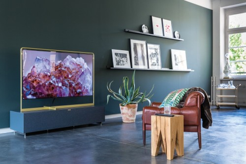 turned-on-television-in-front-of-leather-sofa-chair-and-two-shelf-on-wall-and-frame-on-it-boho-interior-idea-photo.jpg