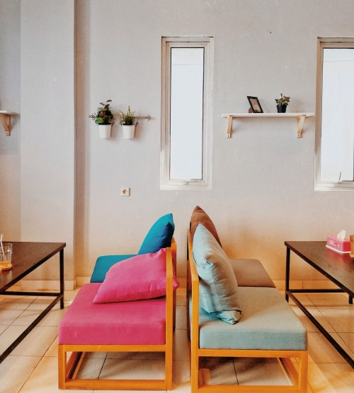 two-brown-wooden-multicolored-padded-chairs-near-coffee-tables-and-white-wall-with-shelf-inside-room-photo.jpg