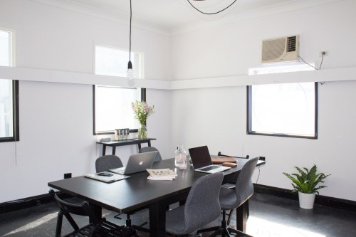 two-laptop-and-bottle-on-rectangular-brown-wooden-table-with-chairs-on-black-surface-inside-home-office-photo.jpg