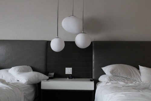 two-white-comforter-set-and-white-table-at-center-and-hanging-white-lamp-above-the-table-photo.jpg