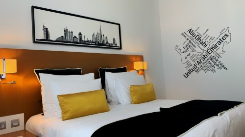 white-and-black-bed-with-orange-and-white-pillow-in-bed-room-and-painting-on-white-wall-photo.jpg