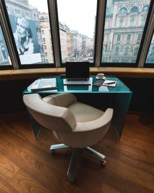 white-and-gray-office-rolling-chair-with-glass-table-near-window-and-outside-country-view-photo.jpg