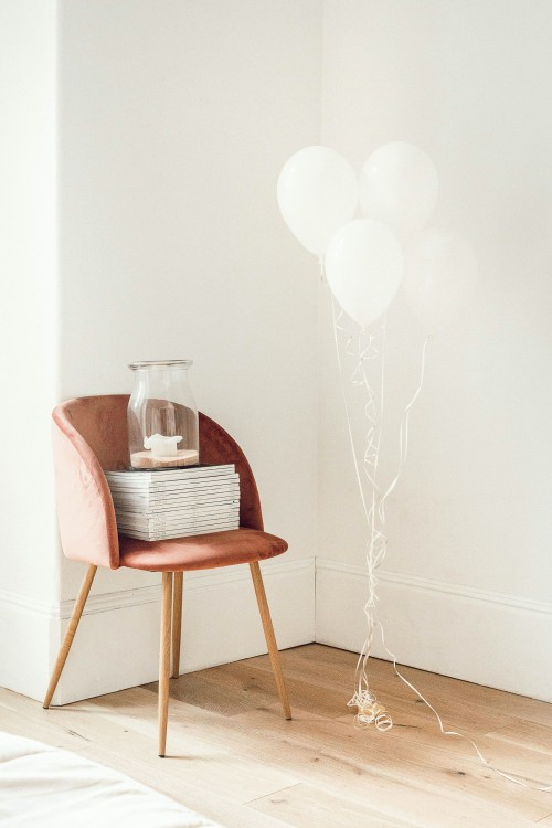 white-balloons-beside-jar-on-book-and-chair-beside-white-wall-photo.jpg