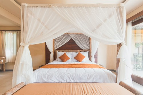 white-curtain-with-brown-wooden-bed-frame-and-fabric-bench-in-front-of-bed-inside-bedroom-photo.jpg