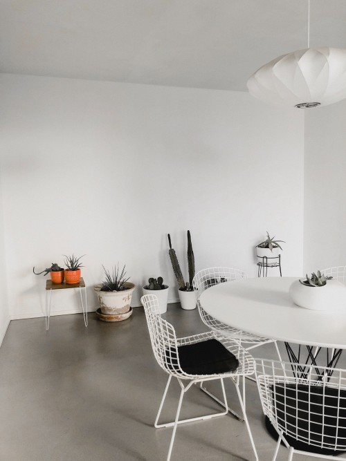 white-oval-table-with-aramless-white-chair-on-brown-surface-and-potted-plant-near-white-wall-photo.jpg