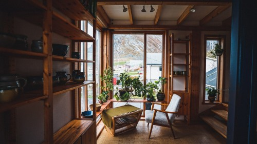 wooden-white-febric-chair-with-table-fronting-window-and-plant-near-window-and-wooden-rack-inside-room.jpg