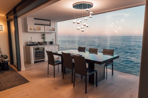 black-dining-table-set-on-brown-surface-placed-beside-glass-window-and-outside-sea-face-dining-room.jpg