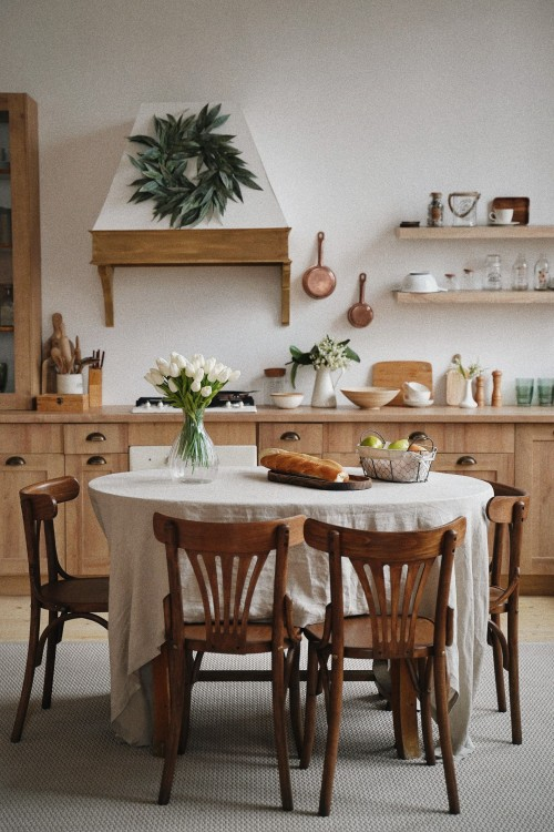 brown-wooden-aramless-chairs-and-table-near-kitchen-counter-and-leaves-frame-on-white-wall-inside-dining-room-photo.jpg