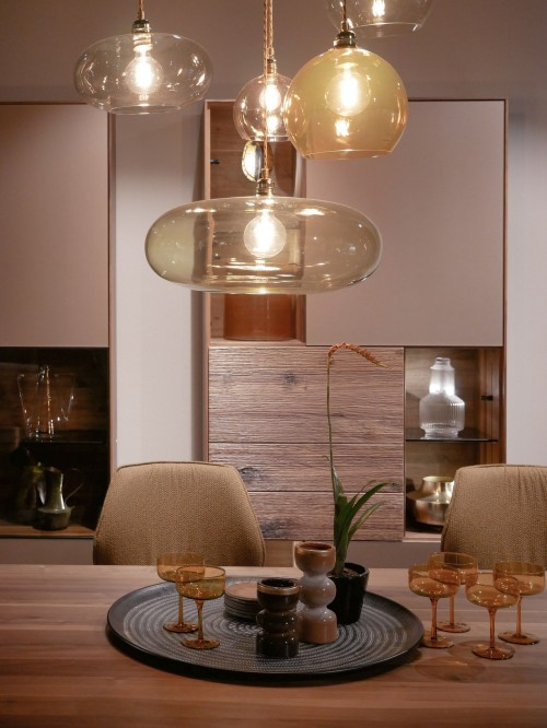 clear-glass-pendant-lamp-turned-on-above-the-dining-table-on-top-cups-and-plates-inside-room-photo.jpg