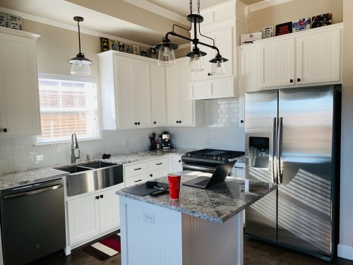 gray-stainless-steel-side-by-side-door-refrigerator-with-water-dispenser-and-three-in-one-hanging-lamp-above-the-table-photo.jpg