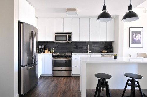 gray-steel-3-door-refrigerator-near-modular-kitchen-and-two-black-hanging-lamp-above-the-kitchen-counter-photo.jpg