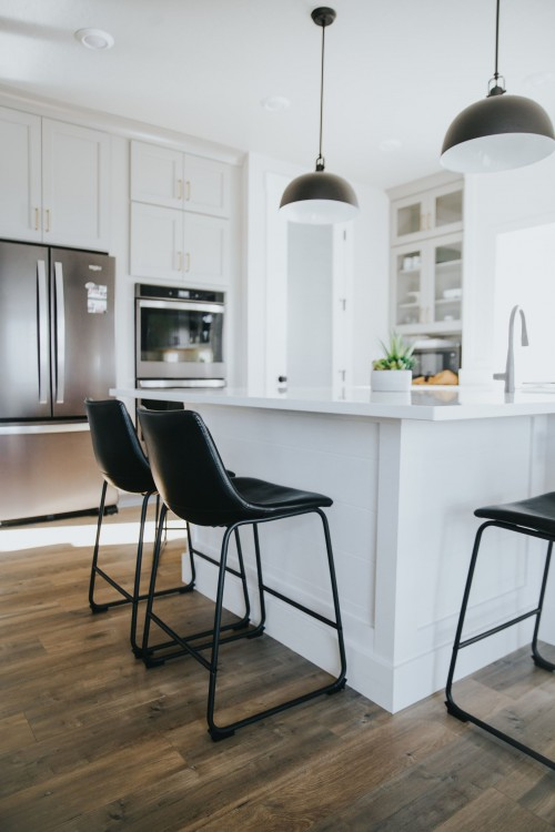 modern-designed-two-black-chairs-and-white-kitchen-counter-and-two-lamp-above-the-counter-and-brown-wooden-surface-inside-kitchen-room-photo.jpg