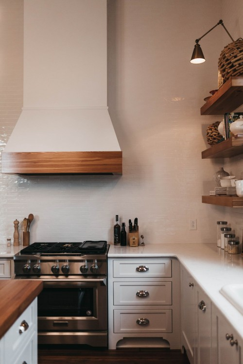 photo-of-clean-kitchen-cupboards-and-wooden-shelf-on-white-wall-and-oven-on-white-kitchen-counter-photo.jpg