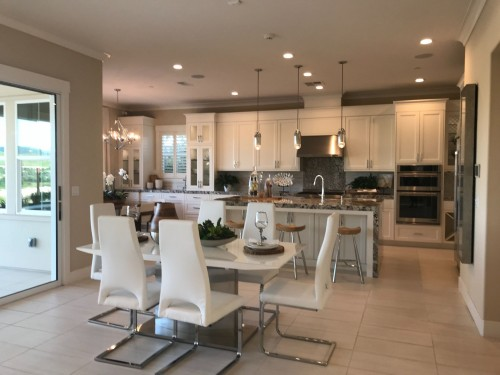 white-dining-table-and-Rmless-chairs-in-front-of-kitchen-counter-with-stainless-steel-faucent-on-kitchen-counter-inside-dining-room-photo.jpg