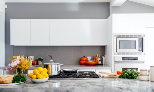 white-over-the-range-oven-fruits-potted-plant-on-kitchen-counter-and-white-plane-drawer-on-brown-wall-photo.jpg