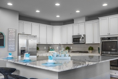white-wooden-kitchen-cabinet-and-cup-and-plates-on-kitchen-table-and-white-drawer-around-the-kitchen-top-photo.jpg
