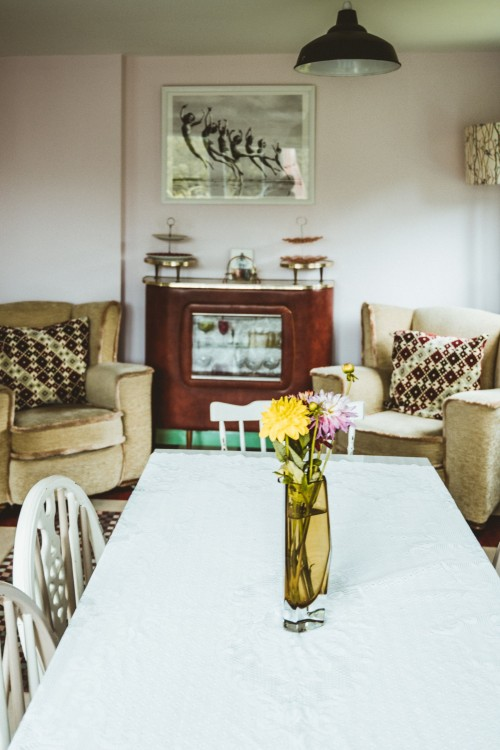 yellow-and-white-flower-on-clear-glass-vase-on-white-dining-set-inisde-room-and-two-sofa-chair-near-white-wall-photo.jpg