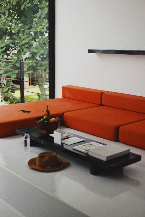 coffee-table-in-front-of-orange-fabric-sectional-sofa-near-glass-window-in-living-room.jpg