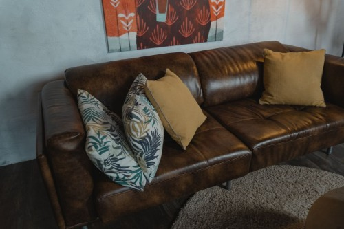 Brown-Leather-Couch-With-White-and-Black-Floral-Throw-Pillow.jpg