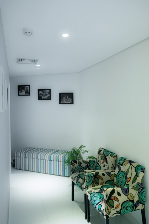 Two-White-and-Green-Floral-Padded-Sofa-Chairs-Next-to-Wall-in-Room.jpg