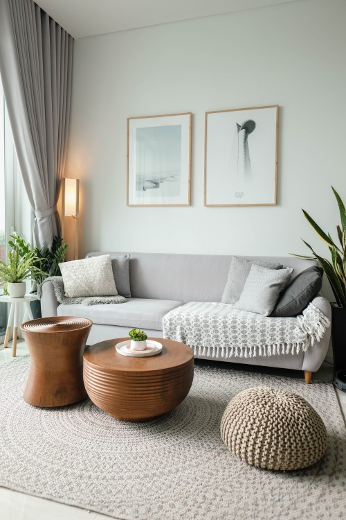 White Theme Living room. Black, Silver, Gray pillows on Metallic Gray Sofa with Round Wooden Coffee Table in Conjunction with Round Puff Ottoman on White Plus gray Circular Design Beside Pin on Lamp at the Back. #LivingRoomDecorationIdeas