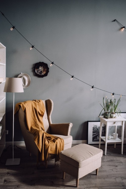 Mid century Modern room interior design gray armchair besides footstool and wired led lights